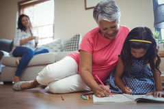 Grootmoeder en kleindochter kleurend boek in het leven stock foto's