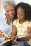 Grootmoeder en kleindochter lezing en het glimlachen stock foto