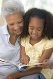 Grootmoeder en kleindochter lezing en het glimlachen Royalty-vrije Stock Foto's