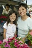 Grootmoeder en kleindochter met bloemen door rug van SUV-portret Royalty-vrije Stock Foto