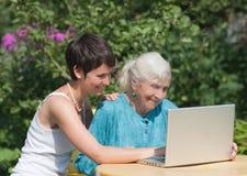 Grootmoeder en kleindochter met laptop stock afbeeldingen
