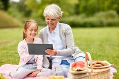Grootmoeder en kleindochter met tablet bij park stock afbeelding