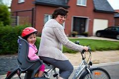 Grootmoeder en kleindochter op fiets Stock Foto's