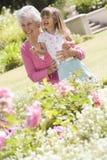 Grootmoeder en kleindochter in openlucht in tuin Stock Foto's