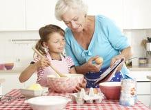 Grootmoeder en Kleindochterbaksel in Keuken Stock Afbeelding