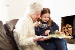 Grootmoeder en Kleindochterlezingsboek thuis samen Stock Foto