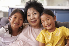 Grootmoeder en Kleindochters die op Sofa At Home ontspannen stock foto