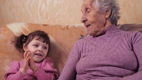 Grootmoeder en kleindochterspel De oma heeft pret thuis met zijn kleindochter op de laag stock footage