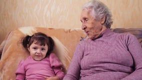 Grootmoeder en kleindochterspel De oma heeft pret thuis met zijn kleindochter op de laag stock videobeelden