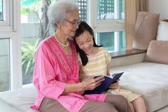 Grootmoeder en kleindochterzitting op bank en lezingsboek h stock afbeeldingen