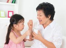 Grootmoeder en kleinkind die yoghurt eten stock afbeelding