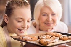 Grootmoeder en kleinkind met koekjes stock foto