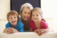 Grootmoeder en Kleinkinderen die op TV Met groot scherm thuis letten Stock Foto's