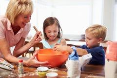 Grootmoeder en Kleinkinderen die samen thuis bakken stock foto