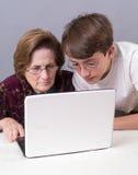 Grootmoeder en kleinzoon die een computer met behulp van Royalty-vrije Stock Foto