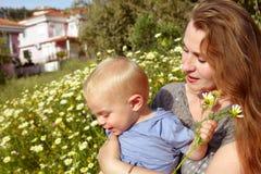 Grootmoeder en kleinzoon op madeliefjesgebied stock fotografie
