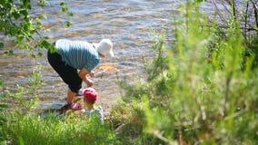 Grootmoeder en kleinzoonvisnet Kust van een bergrivier Koel water op een hete de zomerdag stock video