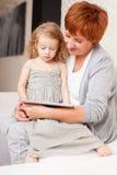 Grootmoeder en meisje thuis op bank stock afbeeldingen
