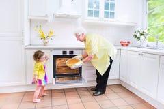 Grootmoeder en meisjebakselpastei in witte keuken stock afbeeldingen