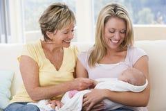 Grootmoeder en moeder in woonkamer met baby