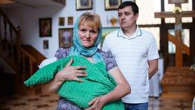 Grootmoeder en peetvader met baby op de doopselceremonie stock foto