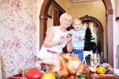 Grootmoeder en weinig jongen die pret op Dankzegging op een vage achtergrond hebben Het concept van de familievakantie royalty-vrije stock foto