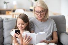 Grootmoeder gelezen boek aan gewijd aan smartphone weinig jong geitje royalty-vrije stock fotografie