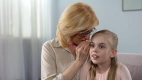 Grootmoeder het fluisteren grootste geheim aan haar kleindochter, de gesprekken van vrouwen stock fotografie