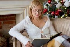 Grootmoeder het ontspannen op een bank voor familiekerstmis stock foto's