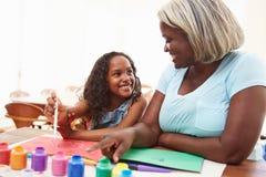 Grootmoeder het Schilderen Beeld met Kleindochter thuis stock foto