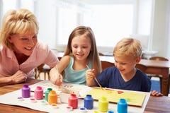 Grootmoeder het Schilderen Beeld met Kleinkinderen thuis Royalty-vrije Stock Foto