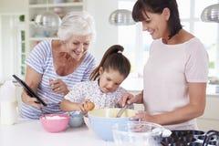 Grootmoeder, Kleindochter en Moederbakselcake in Keuken royalty-vrije stock afbeelding