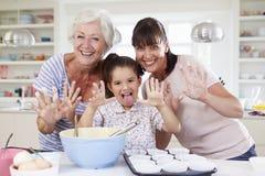 Grootmoeder, Kleindochter en Moederbakselcake in Keuken Stock Fotografie