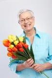 Grootmoeder met bloemen het glimlachen stock afbeelding