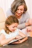 Grootmoeder met de aanrakingstablet van het kleindochtergebruik Royalty-vrije Stock Fotografie