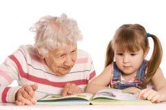 Grootmoeder met de gelezen kleindochter royalty-vrije stock foto's