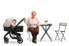 Grootmoeder met een baby in een wandelwagenzitting bij een koffietafel royalty-vrije stock afbeelding