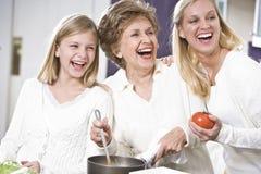 Grootmoeder met familie die in keuken lacht Royalty-vrije Stock Afbeeldingen