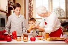 Grootmoeder met grandchilds in keuken, Kerstmis Stock Afbeelding
