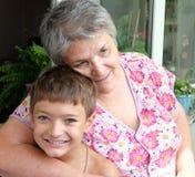 Grootmoeder met haar kleinzoon die samen gelukkig kijken stock foto