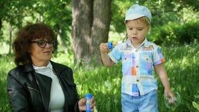 Grootmoeder met kind het rustende spelen in het park Blaas zeepbels op Openlucht recreatie stock videobeelden