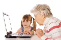Grootmoeder met kleindochter bij de computer royalty-vrije stock afbeeldingen