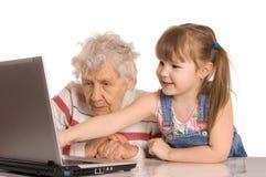 Grootmoeder met kleindochter bij de computer stock afbeeldingen