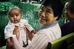 Grootmoeder met kleindochter in een park met vrienden stock fotografie