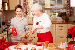 Grootmoeder met kleinkind in keuken, Kerstmis Stock Fotografie