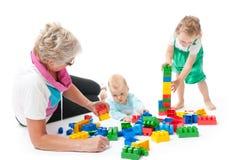 Grootmoeder met kleinkinderen die met blokken spelen stock foto's
