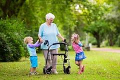 Grootmoeder met leurder het spelen met twee jonge geitjes stock fotografie