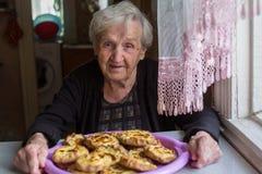 Grootmoeder met pastei in de keuken gelukkig Stock Foto's