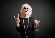 Grootmoeder met zonnebril en drank ter beschikking stock foto's