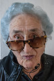 Grootmoeder met zonnebril, hoofdtelefoons en leerjasje Royalty-vrije Stock Afbeelding